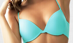 Close-up picture of a woman wearing a turquoise blue bathing suit top, showing the results of a breast reconstruction procedure.