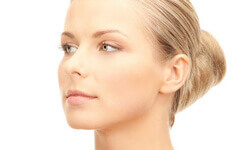 Side view of a woman showing the results of her facelift with necklift procedure.