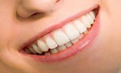 Picture of a smiling patient showing her satisfaction with a holistic periodontal treatment.