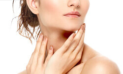 A close-up photo of a woman happy with her neck sculpting procedure.