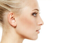 Side profile photo of a woman happy with her nose job (nose surgery) procedure.