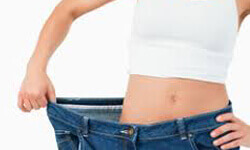Front view photo of a woman standing in oversized jeans illustrating her weight loss with an obesity treatment.