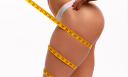 Side view photo of a woman holding a tape measure around her thighs illustrating the results of a thigh reduction procedure.