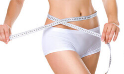 Picture of a woman holding a tape measure around her, showing the results of a vibroliposuction procedure.