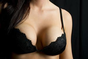 Close-up picture of a slender woman's breasts under a black bra, displaying the breast lift with reduction procedure she had in Costa Rica.