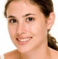 Close-up picture of a smiling woman facing the camera, displaying the buccal fat pad removal procedure she had in Costa Rica.