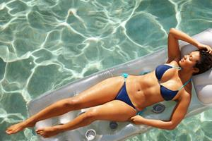 Picture of a slender woman lying on a float in a pool, displaying her abdomen, hips and waist liposuction she had in Costa Rica.