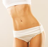 Picture of trim woman wearing white shorts and a white halter, showing the results of the hips liposuction procedure she had in Costa Rica.