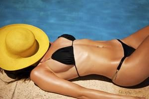 Picture of a beautiful woman, lying on a beach blanket on the sand, displaying the liposuction procedure she had in Costa Rica.
