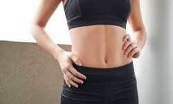 Picture of a woman in a two piece matching halter and shorts outfit showing her abdomen, hips and hips liposuction procedure she had in Costa Rica.