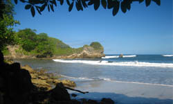 Picture of a beautiful Costa Rica beach with waves breaking on a sandy shore.