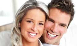 Picture of a smiling couple, standing, proud of their dental treatment in Costa Rica