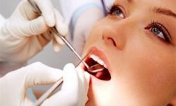 Picture of a smiling woman in a dental chair as a dentist is extracting a tooth.