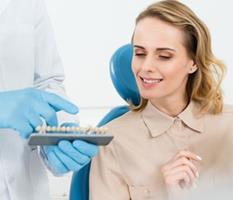 Picture of a smiling woman sitting in a dental chair, illustrating the availability of holistic ceramic dental implants procedure in Costa Rica.