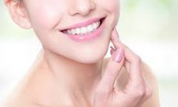 Picture of a smiling woman holding a hand to her jaw showing her happiness with the holistic oxygen dental treatment she had.
