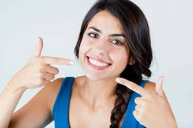 Picture of a smiling woman showing her happiness with the holistic periodontal treatment she is receiving.