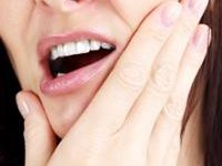 Picture of a woman holding a hand under her chin, showing her happiness with the holistic temporo-mandibular treatment she had in Costa Rica.