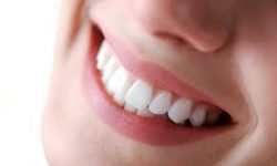 Picture of a smiling woman holding with invisible braces on her teeth, showing her happiness with the Invisalign invisible braces aligners procedure she had in Costa Rica.