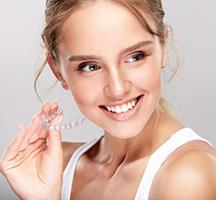 Picture of a smiling woman holding invisible braces, showing her happiness with the Invisalign invisible braces procedure she had in Costa Rica.
