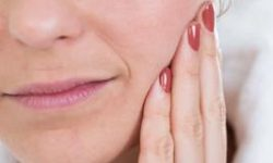 Picture of a woman with her head slightly tilted and with her hand on her cheek, showing the area of orofacial pain.
