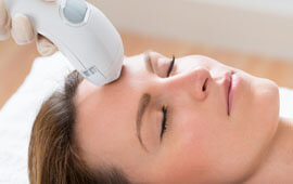 Picture of a woman lying down, and having a Fractional CO2 laser treatment.